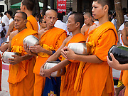 08 SEPTEMBER 2013 - BANGKOK, THAILAND: Buddhist monks stand on Rajadamri Road after a mass alms giving ceremony in Bangkok. 10,000 Buddhist monks participated in a mass alms giving ceremony on Rajadamri Road in front of Central World shopping mall in Bangkok. The alms giving was to benefit disaster victims in Thailand and assist Buddhist temples in the insurgency wracked southern provinces of Thailand.       PHOTO BY JACK KURTZ