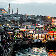 The busy waterfront district of Eminonu in Istanbul, at the foot of the Galata Bridge. Suleymaniye Mosque is in the background.