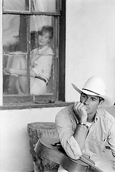 cowboy at home and a woman looking on through a window