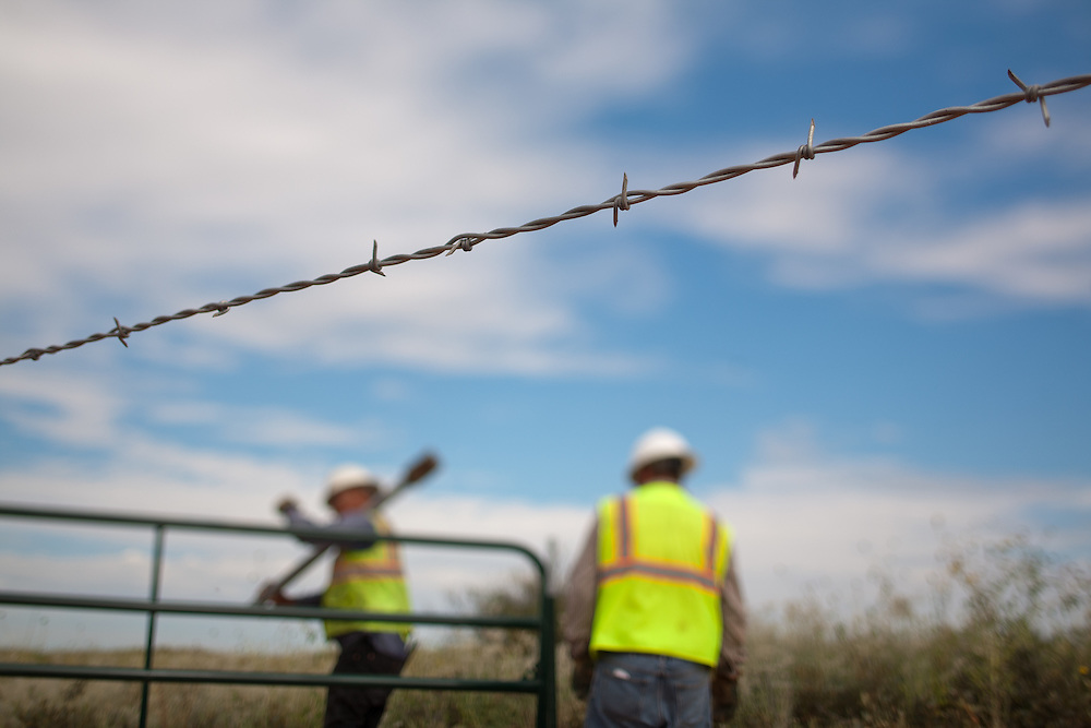 A construction crew works on a fence along the new highway under construction near The Waste Isolation Pilot Plant in Eddy County. WIPP received $172 million as part of the Recovery and Reinvestment Act. The highway will increase access for trucks carrying nuclear waste to the WIPP.
