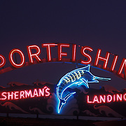 """Colorful neon sign,lit up at dusk, reading """"Sportsfishing, Fisherman's Landing"""" at Pt Loma sports fishing establishment, H&M Landing in San Diego. Blue neon tuna is on the sign."""
