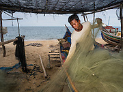 15 JUNE 2105 - BAN THONG, NARATHIWAT, THAILAND:  Subsistence fishermen in Ban Thong stow their nets on a small fishing boat.      PHOTO BY JACK KURTZ