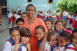 Teacher in playground of primary school in Havana; Cuba; surrounded by children,
