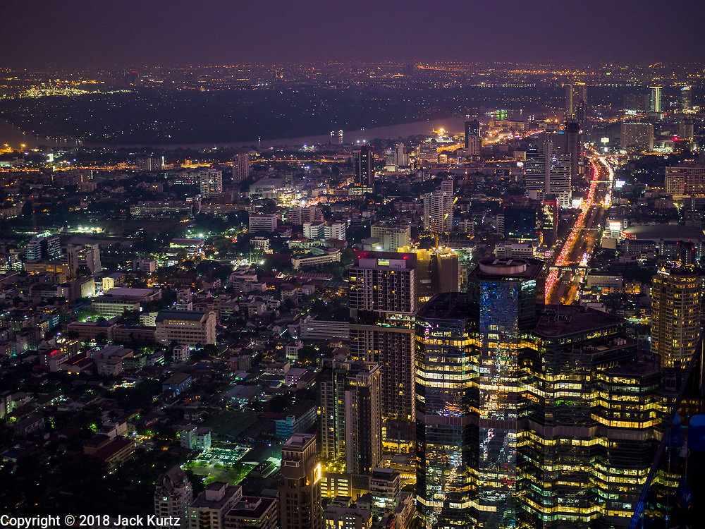 27 DECEMBER 2018 - BANGKOK, THAILAND:  Looking south after sunset from the rooftop observation deck of the King Power Maha Nakhon Tower. The Chao Phraya River is in the upper third of the frame. The MahaNakhon Skywalk, at the top of the King Power Maha Nakhon Tower, is 1,030 feet (314 meters) above street level. It is the tallest building and highest vantage point in Bangkok. The skywalk opened in November and has been drawing large crowds.    PHOTO BY JACK KURTZ