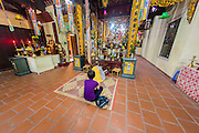 01 APRIL 2012 - HANOI, VIETNAM:  A Buddhist monk prays in Chua Cau Dong Temple in Hanoi, the capital of Vietnam. Eastern Gate Pagoda, or Chua Cau Dong, is a temple in the Old Quarter of Hanoi. This elaborately ornate temple is said to be nearly a thousand years old.    PHOTO BY JACK KURTZ