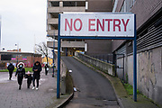 People out pass a No Entry sign in the City Centre as tier three / very high alert level of the Coronavirus tier system continues during the run up to Christmas on 14th December 2020 in Birmingham, United Kingdom. After 9 months of lockdown in various forms, people are used to navigating the rules of shopping safely as all non-essential shops try to increase their takings and onwards to the national economy.