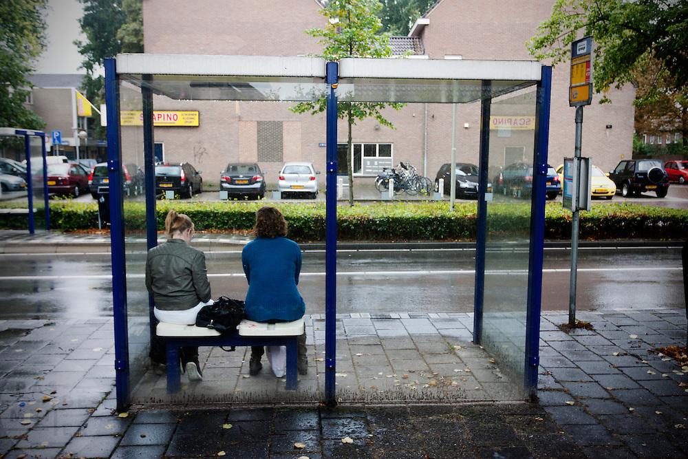 Twee meisjes wachten bij een bushalte in Zevenaar.<br /> <br /> Two girls are waiting at a busstop in Zevenaar.