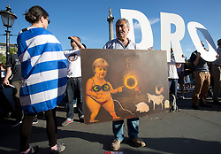 © Licensed to London News Pictures. 29/06/2015. London, UK. Artist Kaya Mar holds one of his satirical paintings at the demonstration organized by Solidarity with Greece at Trafalgar Square, central London, as they call for the Greek debt to be wiped. Photo credit: LNP