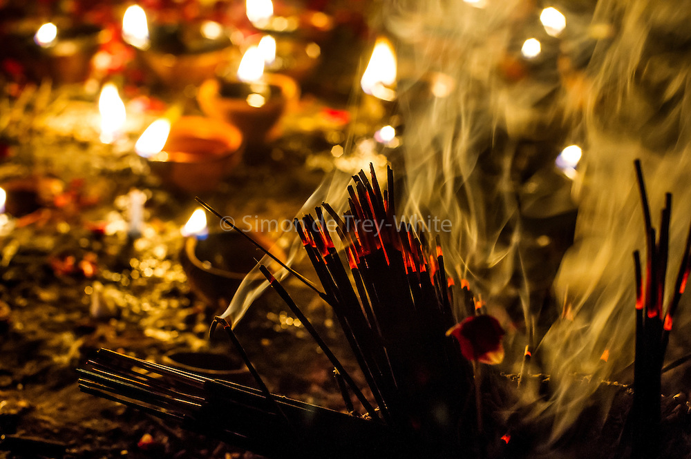 "8th January 2015, New Delhi, India. Incense sticks and oil lamps left by believers hoping to get their wishes granted by Djinns burn in the ruins of Feroz Shah Kotla in New Delhi, India on the 8th January 2015<br /> <br /> PHOTOGRAPH BY AND COPYRIGHT OF SIMON DE TREY-WHITE a photographer in delhi<br /> + 91 98103 99809. Email: simon@simondetreywhite.com<br /> <br /> People have been coming to Firoz Shah Kotla to leave written notes and offerings for Djinns in the hopes of getting wishes granted since the late 1970's. Jinn, jann or djinn are supernatural creatures in Islamic mythology as well as pre-Islamic Arabian mythology. They are mentioned frequently in the Quran  and other Islamic texts and inhabit an unseen world called Djinnestan. In Islamic theology jinn are said to be creatures with free will, made from smokeless fire by Allah as humans were made of clay, among other things. According to the Quran, jinn have free will, and Iblīs abused this freedom in front of Allah by refusing to bow to Adam when Allah ordered angels and jinn to do so. For disobeying Allah, Iblīs was expelled from Paradise and called ""Shayṭān"" (Satan).They are usually invisible to humans, but humans do appear clearly to jinn, as they can possess them. Like humans, jinn will also be judged on the Day of Judgment and will be sent to Paradise or Hell according to their deeds. Feroz Shah Tughlaq (r. 1351–88), the Sultan of Delhi, established the fortified city of Ferozabad in 1354, as the new capital of the Delhi Sultanate, and included in it the site of the present Feroz Shah Kotla. Kotla literally means fortress or citadel."