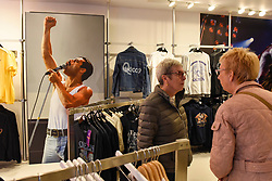 "© Licensed to London News Pictures. 18/10/2018. LONDON, UK.  Visitors to the Queen pop-up shop which has opened in Carnaby Street.  Coinciding with the release next week of the movie ""Bohemian Rhapsody"", the shop offers Queen music fans memorabilia, a display of stage costumes as well as archived Queen performance footage.  Photo credit: Stephen Chung/LNP"