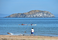A fisherman on the beach at North Berwick looks on as two sea kayakers pass by with Craigleith Island in the distance on the first day of phase 1 of the reduction in Covid lockdown in Scotland.<br /> <br /> © Dave Johnston / EEm