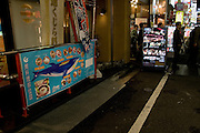 """A useful sign outside a restaurant in Shinjuku's red light district, Kabukicho, showing the prime cuts from a whale  - presumably caught under Japan's """"scientific"""" research programme. Next door, a sign advertises """"Girls""""."""