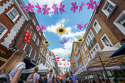 © Licensed to London News Pictures. 16/06/2021. LONDON, UK.  People pass beneath a Botanical Garden installation which has been unveiled overhead by property company Shaftesbury plc, transforming the sky across Chinatown London's Gerrard Street.  The display is inspired by tranquil inner-city gardens that can be found across East and Southeast Asia (ESEA and showcases seven different species of flower, including Chinese Peonies, Peach Blossom, and Orchids.  The display is on show until 31 August.  Photo credit: Stephen Chung/LNP
