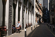 A city worker sits in afternoon sunshine on Throgmorton Street during the Coronavirus pandemic in the City of London, the capitals financial district, on 30th July 2020, in London, England.  city worker sitting on a bar stool outside a pub on Throgmorton Street during the Coronavirus pandemic in the City of London, the capitals financial district, on 30th July 2020, in London, England.