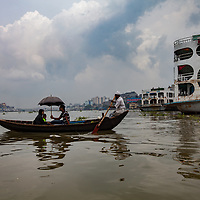 a small boat is ferried across the Buriganga river with a family, Dhaka, Bangladesh