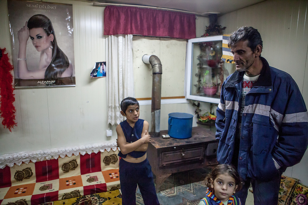 Inside in one of the new housing facilities in Konik Camp located in the suburbs of the city of Podgorica, Montenegro. Fadilj Sahiti (right) with two of his children in their home. He was born 1968 worked originally as  a musician and is father of four children. He arrived 1999 as a refugee from Kosovo at the Konik Camp. Mr. Sahiti has no papers, is not allowed to work oficially and gets no financial support.