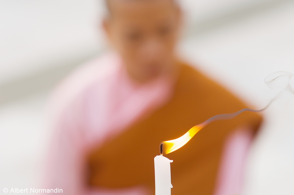 Candle burning with Nun in pink praying, out of focus, at Shwedagon Pagoda