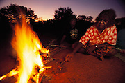 Pauline Woods cooks witchetty grubs in the ashes of a campfire as her daughter watches, outside Alice Springs, Australia. Witchetty grubs are the larvae of cossid moths. The large white worms live in tunnels in the ground where they feed on sap from the roots of a species of Acacia, commonly known as Wichetty Bush. (Man Eating Bugs: The Art and Science of Eating Insects)