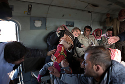 © Licensed to London News Pictures. 11/12/2014. Sinjar Mountains, Iraq. A young Yazidi refugee is handed through the door of Iraqi Air Force Mi-17 Hip helicopter by his or her mother as they are evacuated from Mount Sinjar.<br /> <br /> Although a well publicised exodus of Yazidi refugees took place from Mount Sinjar in August 2014 many still remain on top of the 75 km long ridge-line, with estimates varying from 2000-8000 people, after a corridor kept open by Syrian-Kurdish YPG fighters collapsed during an Islamic State offensive. The mountain is now surrounded on all sides with winter closing in, the only chance of escape or supply being by Iraqi Air Force helicopters. Photo credit: Matt Cetti-Roberts/LNP