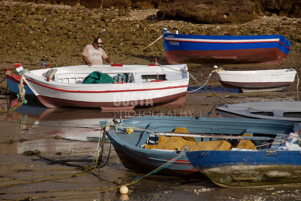 ESPAÑA / ANDALUCÍA / CÁDIZ.Un pescador pintando su barca en la Playa de la Caleta...