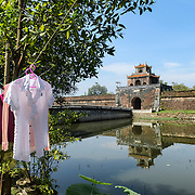 Local residents on the other side of the moat hang out their washing to dry at the Imperial City in Hue, Vietnam. A self-enclosed and fortified palace, the complex includes the Purple Forbidden City, which was the inner sanctum of the imperial household, as well as temples, courtyards, gardens, and other buildings. Much of the Imperial City was damaged or destroyed during the Vietnam War. It is now designated as a UNESCO World Heritage site.