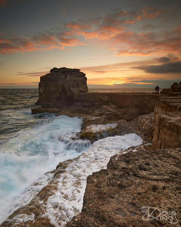 A romantic couple enjoy the sunset together beside the Pulpit Rock whilst ocean waves break over the rock ledges behind them.
