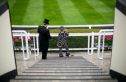 © Licensed to London News Pictures. 19/06/2018. London, UK.  A woman poses for a photograph in an elaborate hat at day one of Royal Ascot at Ascot racecourse in Berkshire, on June 19, 2018. The 5 day showcase event, which is one of the highlights of the racing calendar, has been held at the famous Berkshire course since 1711 and tradition is a hallmark of the meeting. Top hats and tails remain compulsory in parts of the course. Photo credit: Ben Cawthra/LNP