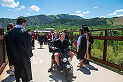 Aspen High School graduate John Doyle drives his scooter over the Tiehack Bridge with fellow graduate Jamison Delaney on the back after the 2021 commencement ceremony in Aspen, Colorado.