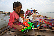 FISHERMEN MEKONG RIVER. South East Asia, Cambodia, Phnom Penh, Mekong River. The Cham fisher people live in various desolated villages along the banks of the Mekong and Tonle Sap rivers. The fisher families live like river gypsy nomads, working and living on their boats, sleeping under a sprung bamboo frame, all their worldly goods stored below deck. They live in extended families, with numerous boats, together for safety. Their diet is rice, vegetables and fish. Their sleek wooden boats are powered by petrol outboard motors with batteries or generators to supply lighting at night. Their fishing technique is laying nets twice or three times per day, which are weighted well below the surface, using old paint aerosal canisters as buoyant floaters, hanging just beneath the surface. These particular fisher families, living at the junction of the Mekong and Tonle Sap rivers, overlooked by Phnom Penh, sell their catch at the Vietnamese market, on the banks of the river. Their life and fortunes are controlled by the cycle of the river. As the river levels drop, so the quantity of fish decreases, until after the heavy floods of the monsoon they fill the river again. They are poor traditional Muslims, marginalised from mainstream society, living a third world life in the immmediate shadow of the first world. The Cham, originally a people of an ancient kingdom called Champa, are a small and disenfranchised community who were disinherited of their land. They are a socially important ethnic group in Cambodia, numbering close to 300,000. The Cham people, live in some 400 villages across Kampong Chnang and Kampong Cham provinces. Their religion is Muslim and their language belongs to the Malayo-Polynesian family. Their livelihoods are as diverse as rice farming, cattle trading, hunting and fishing.///Cham fisher family on their riverboat going to market at Phnom Penh. Sok Ray with his wife Ty Cho, and their son Sary, and daughters Baisas, 14, Apini 9 years, and Asimas, 3 years ol
