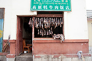 Shop selling dried beef which is a speciality of the area on the streets of Zhongdian, also known as Shangrila, Yunnan; China. This is a very normal scene in this wild town.