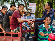 """15 FEBRUARY 2019 - SIHANOUKVILLE, CAMBODIA: Chinese construction workers in Sihanoukville are shuttled to their job site in a large tuk-tuk. There are about 80 Chinese casinos and resort hotels open in Sihanoukville and dozens more under construction. The casinos are changing the city, once a sleepy port on Southeast Asia's """"backpacker trail"""" into a booming city. The change is coming with a cost though. Many Cambodian residents of Sihanoukville  have lost their homes to make way for the casinos and the jobs are going to Chinese workers, brought in to build casinos and work in the casinos.     PHOTO BY JACK KURTZ"""