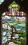 Stained glass window church of Saint Mary, Martlesham, Suffolk, England, UK by Walter J Pearce in Arts and Craft style, 1903 Shepherd and Flock detail wolf attacking sheep