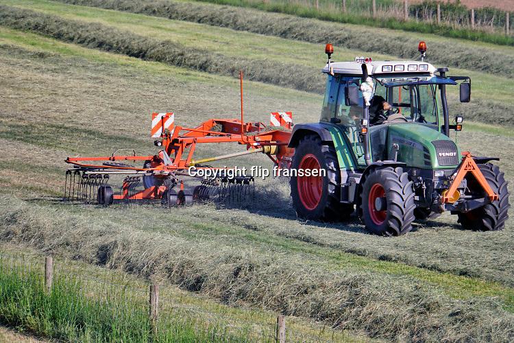 Nederland, Oosterhout, 26-5-2020 In de uiterwaarden van de rivier de Waal is een boer bezig met gras binnenhalen. Daarna wordt het tot balen hooi verpakt en als wintervoer aan het vee, de koeien, gevoerd. Door de aanhoudende droogte groeit het gras minder hard waardoor er minder binnengehaald kan wordenFoto: Flip Franssen