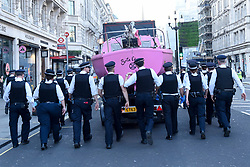 """© Licensed to London News Pictures. 19/04/2019. LONDON, UK.  Police officers form a cordon around the pink boat as it is removed from Oxford Circus during """"London: International Rebellion"""", on day five of a protest organised by Extinction Rebellion.  Protesters are demanding that governments take action against climate change.  Police have issued a section 14 order requiring protesters to convene at Marble Arch only so that the protest can continue.  Photo credit: Stephen Chung/LNP"""