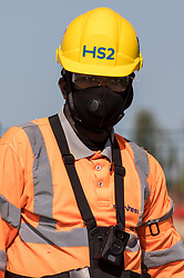 West Hyde, UK. 14th September, 2020. A HS2 security guard watches environmental activists from HS2 Rebellion who blocked a gate to the South Portal site for the HS2 high-speed rail link. Anti-HS2 activists blocked two gates to the same works site for the controversial £106bn rail link, one remaining closed for over six hours and another for over nineteen hours.
