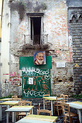 An image of Padre Pio hung from a balcony of a derelict building that overlooks the tables of a cafe Naples, Italy.<br /> Padre Pio, also known as Saint Pio of Pietrelcina Pio da Pietrelcina was a friar, priest, stigmatist, and mystic now venerated as a saint of the Catholic Church. <br /> He was both beatified 1999 and canonized 2002 by Pope Saint John Paul II.