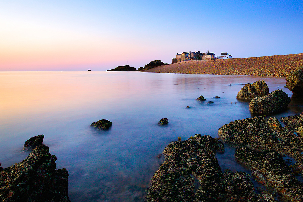 Pink sky at sunrise reflecting over the glass calm clear water at the Ecrehous, a tourist destination in Jersey, Channel Islands