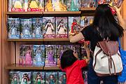 Visitors look through a shelf of doll for sale at Walt Disney Co.s Shanghai Disneyland theme park  towards the iconic castle during a trial run ahead of its official opening, in Shanghai, China, on Wednesday, June 8, 2016. The $5.5 billion Shanghai Disneyland is one  of the most profitable Disney ventures in the world and the first theme park on mainland China.