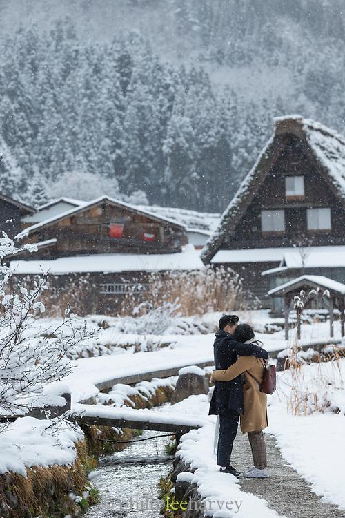 Couple embracing in snow in Shirakawa-go, Japan