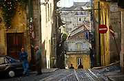 The steep countours of Lisbon's Rua de Bica de Quarte Belo in the Portuguese capital's Bica district. With the rails of the funicular tram disappears over the edge, two local men stand and talk on a flatter part of this steep street in one of the oldest parts of the Portuguese capital. The Bica Funicular is a funicular railway that forms the connection between the Calçada do Combro/Rua do Loreto and the Rua de S. Paulo and opened on 28 June, 1892. It climbs the Rua da Bica de Duarte Belo for 245 metres from the Rua S. Paulo.