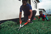 Simon Qampie cuts the grass around his family's tiny house in the sprawling area of Southwest Township (called Soweto), outside Johannesburg (Joberg), South Africa. Published in Material World: A Global Family Portrait, pages 22-23. Material World Project.