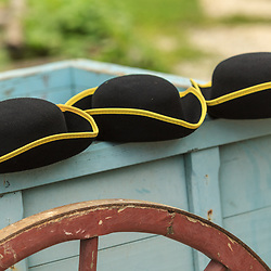 Three colonial men's hats sit on the edge of a wagon.