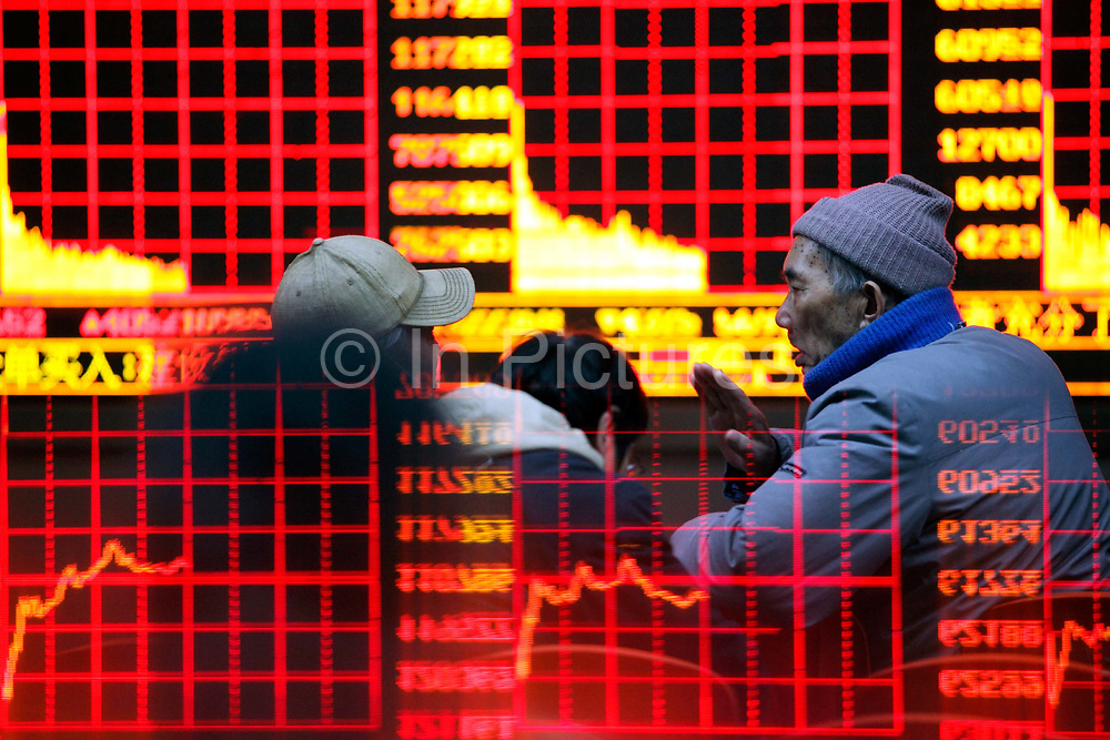Investors watch the stock trading board as the board itself is reflected on a counter top at a securities exchange house in Shanghai, China on 11 January 2010.   Despite the country's robust economy, China's stock market has not been kind to the ordinary investors, it is one of the worst performing major markets in recent years.