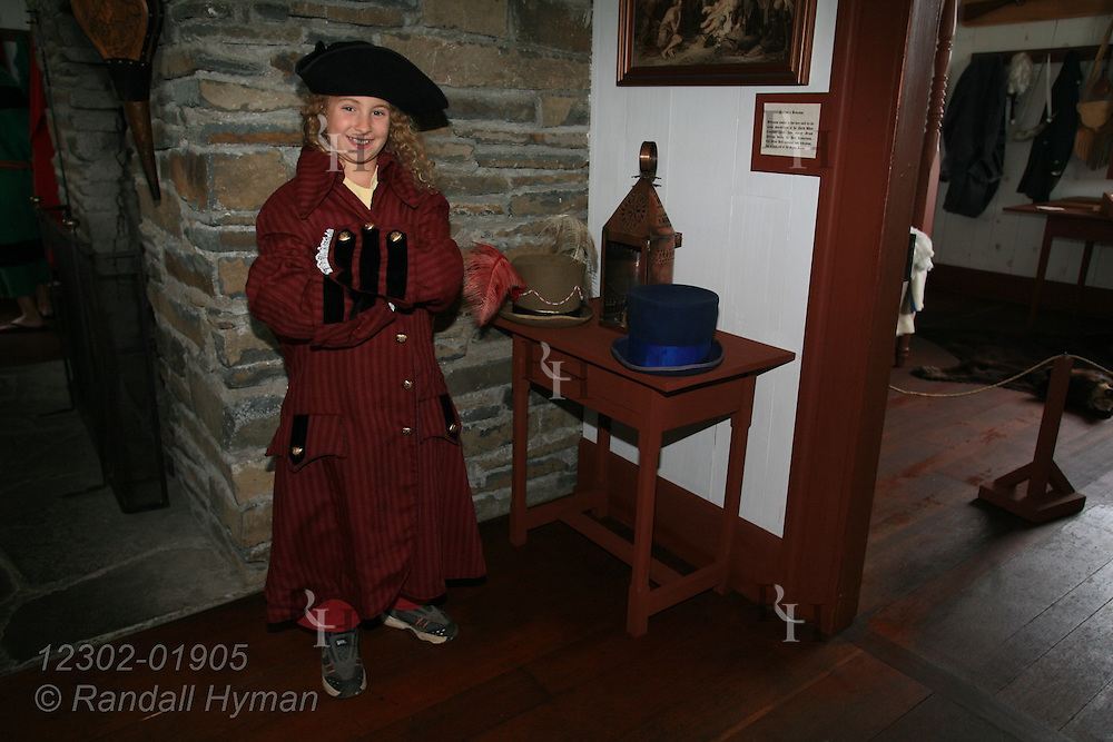 Young girl dresses up like Alexander Mackenzie in great hall of reconstructed 18th-century North West Company trading post; Grand Portage National Monument, Minnesota.