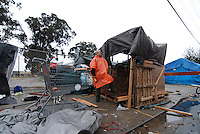 A relative of a homeless Chinatown resident tries to make what he can out of a collapsed structure on Market Way in Salinas.