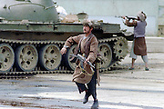 An Afghan mujahideen fighter with Jamayat-E-Islami forces during fighting against Hezb-i Islami following the fall of the capital April 19, 1992 in Kabul, Afghanistan. Fighting between mujahideen factions began almost immediately after they captured the city.