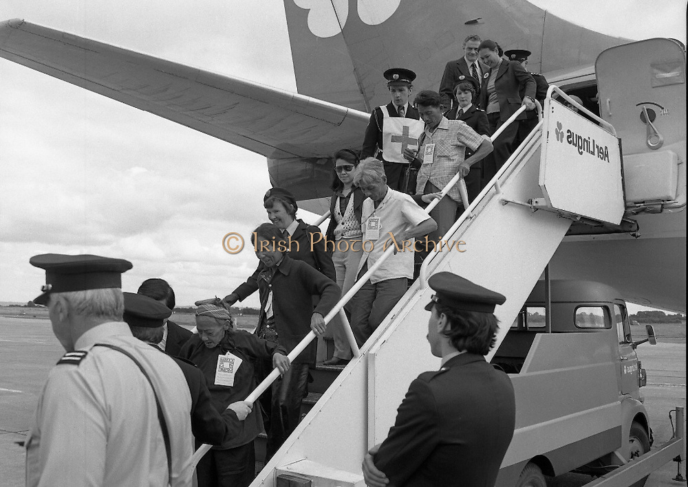 Vietnamese Refugees Arrive In Ireland.   (M85)..1979..09.08.1979..08.09.1979..9th August 1979..As part of an UNHCR initiative, Ireland agreed to take some of the Vietnamese (boat people) refugees into the country. A temporary refugee centre has been set up in the grounds of Blanchardstown Hospital to accomodate the families, from where they will be assimilated into the community..Image shows refugees both young and old being assisted from the aircraft by the Irish Red Cross Volunteers and members of the airport police.
