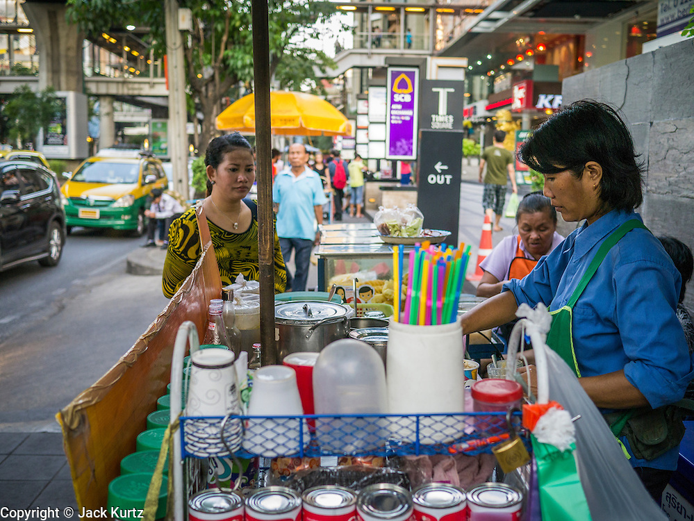"""30 MARCH 2013 - BANGKOK, THAILAND: A coffee vendor makes a drink for a customer on an upscale stretch of Sukhumvit Road in Bangkok. Thailand's economic expansion since the 1970 has dramatically reduced both the amount of poverty and the severity of poverty in Thailand. At the same time, the gap between the very rich in Thailand and the very poor has grown so that income disparity is greater now than it was in 1970. Thailand scores .42 on the """"Ginni Index"""" which measures income disparity on a scale of 0 (perfect income equality) to 1 (absolute inequality in which one person owns everything). Sweden has the best Ginni score (.23), Thailand's score is slightly better than the US score of .45.  PHOTO BY JACK KURTZ"""