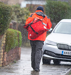 ©Licensed to London News Pictures 27/02/2020<br /> Orpington, UK. A postman working as the snow falls. Snowy weather this morning in Orpington, South East London. Photo credit: Grant Falvey/LNP
