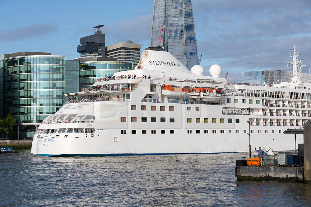 © Licensed to London News Pictures. 01/08/2017. LONDON, UK.  Silver Wind, a huge 514 feet long, 17,400 ton cruise liner leaves London under Tower Bridge this morning after a brief visit, towed backwards by two tugs. Silver Wind carries just 296 passengers and its owner, Silversea claim that the ship has amongst the highest space-to-guest ratios in the cruise ship industry, with the largest suites measuring 1,314 square feet. Tickets cost thousands of pounds, but all guest expenses, even champagne are included in the price. Environmentalists claim thepollutioncreated by giantcruise ships outweigh their economic benefits. The Port of London Authority (PLA) are conducting a work programme during 2017 to monitor air quality and pollution caused by river traffic on the River Thames.  Photo credit: Vickie Flores/LNP